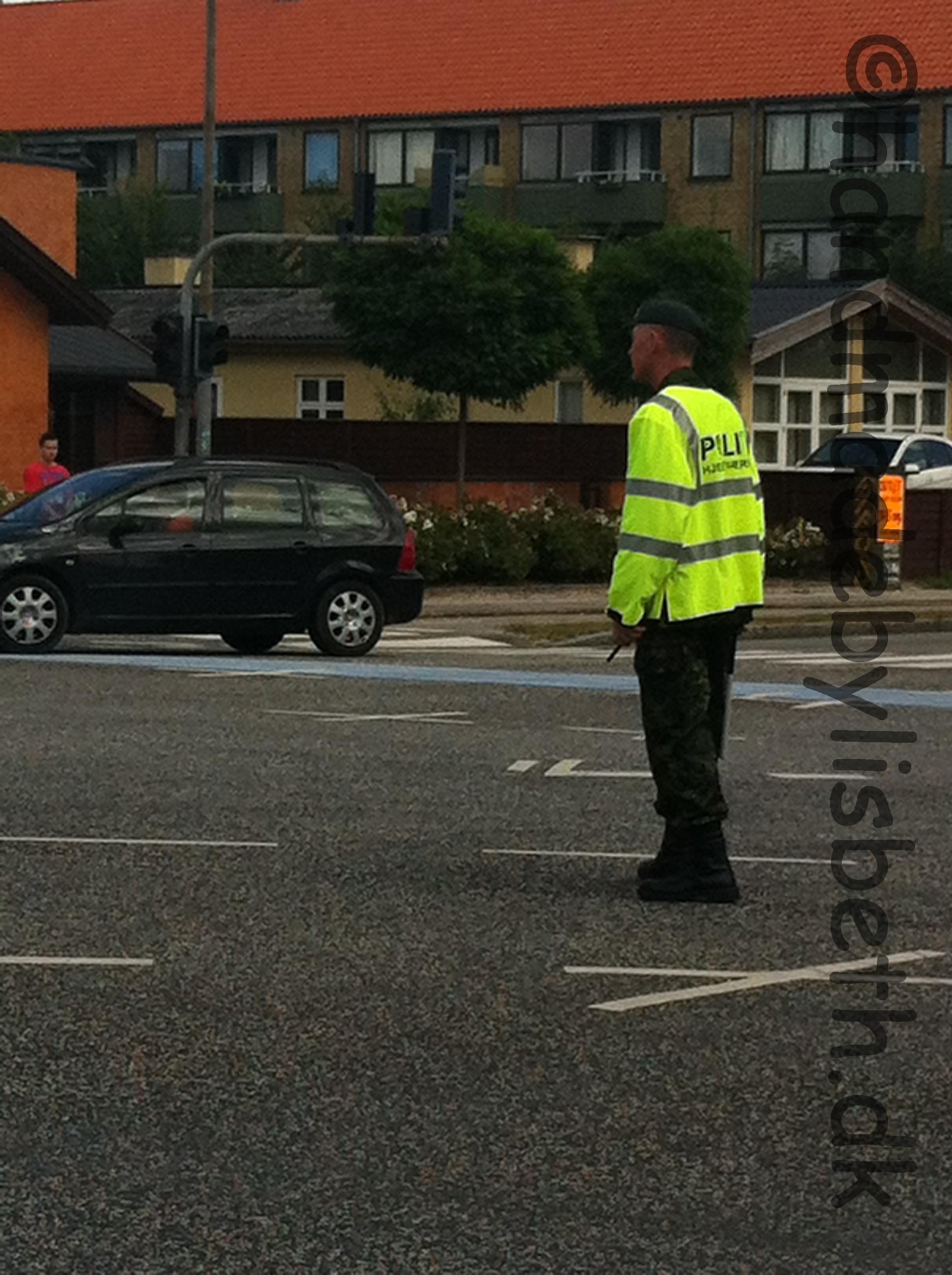 Post Danmark rundt 2013  Hjemmeværnet forsøger at styre trafikken, mens vi venter på rytterne. Helst modsat af farverne på lyskurven, så kan han nemlig få lov til at skælde lidt ud. Tilgengæld er vi tilskuere underholdt....